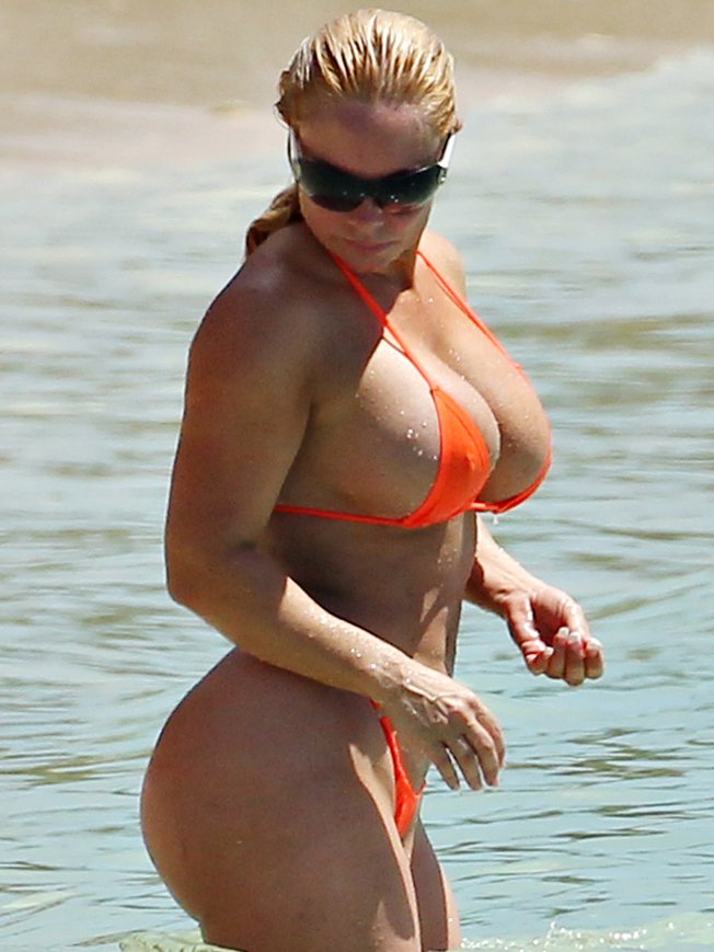 Reality star Coco Austin shows off her assets in a string orange